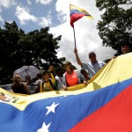 Pro-government supporters holding Venezuela's flag march in Caracass